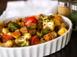 a sheet pan meal with tomatoes, broccoli, cauliflower, sweet potatoes, and beef